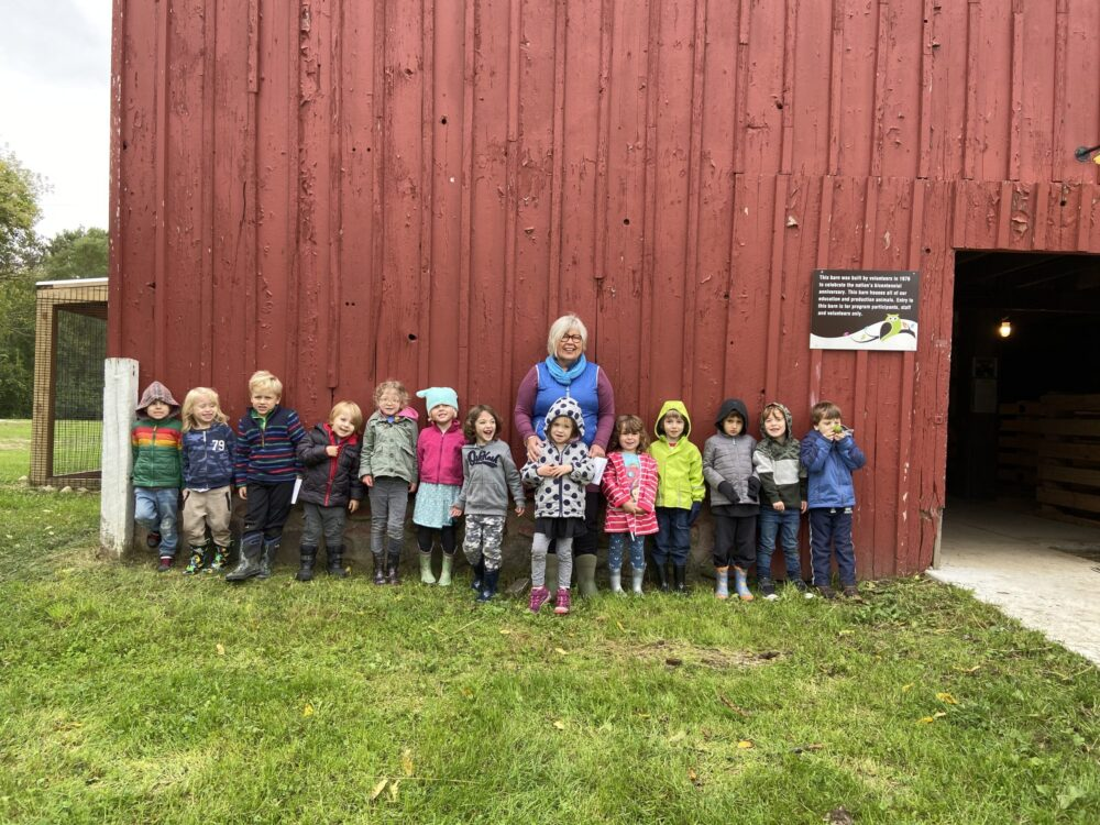 Mrs. Wilson and students by red barn wall